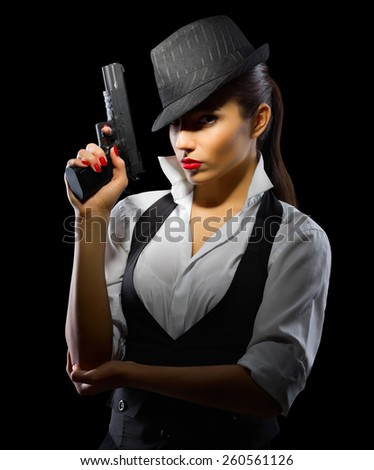 Young girl with gun on black - stock photo