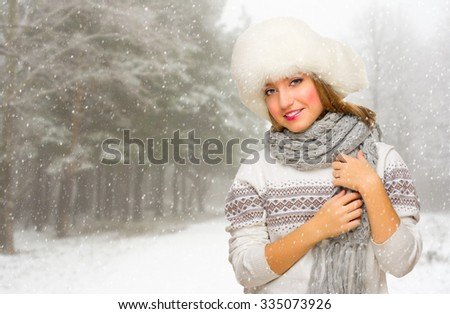 Young girl with hat at snowy winter forest - stock photo