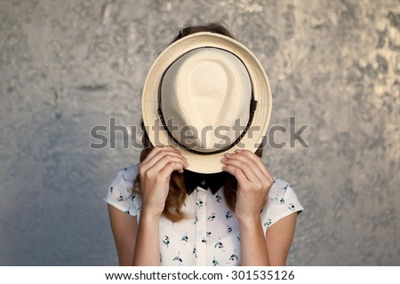 Young girl with hat. Hides her face.Depression.Photo tinted and styled with vintage photo. - stock photo