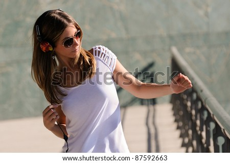 Young girl with headphones and sunglasses dancing in the street - stock photo