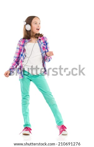 Young girl with headphones singing and dancing. Full length studio shot isolated on white. - stock photo