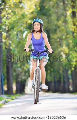 Young girl with helmet riding a bicycle outdoors