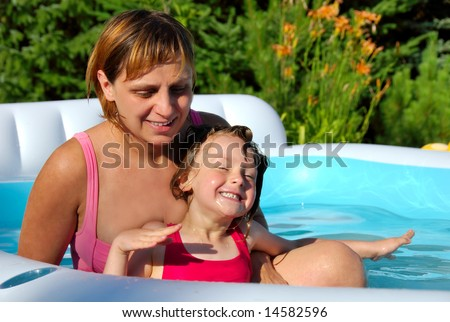 Young girl with her mum in the pool - stock photo
