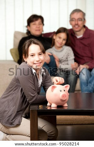 young girl  with her parents and daughter saving money on a piggy bank - stock photo