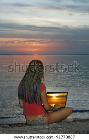 Young girl with laptop on sea shore on sunset background - stock photo