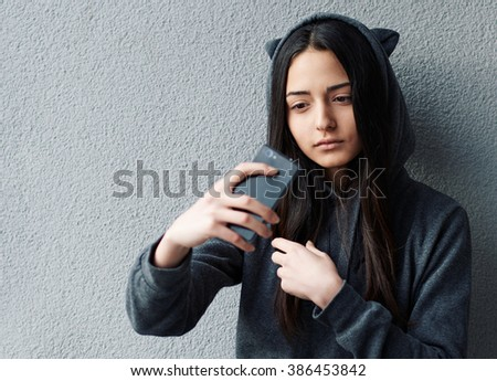 Young girl with long black hair in hood making selfie against of white textured wall. - stock photo