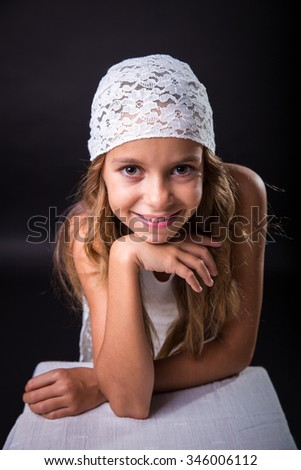 Young girl with long hair and cap smiling on black background - stock photo