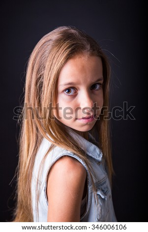 Young girl with long hair and denim jacket posing with a sober look on a black background - stock photo