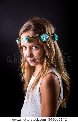 Young girl with long hair and flower tiara posing with a sober look on a black background - stock photo