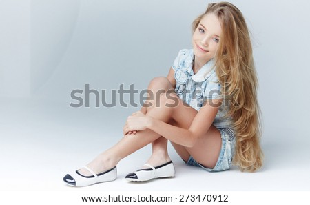 Young girl with long hair in jeans shorts and tshirt sitting on the floor. Isolated on grey - stock photo