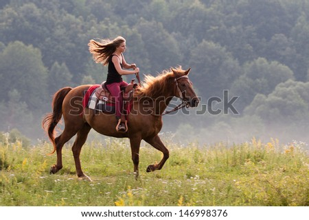 Young girl with long hair riding galloping horse breed Quarter - stock photo
