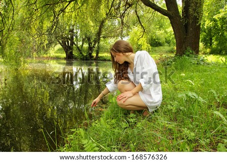 Young girl with long hair sitting near the lake in the shade