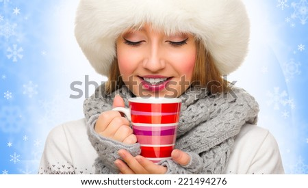 Young girl with mug on blue snowy background - stock photo