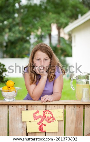 Young girl with no customers at her lemonade stand - stock photo