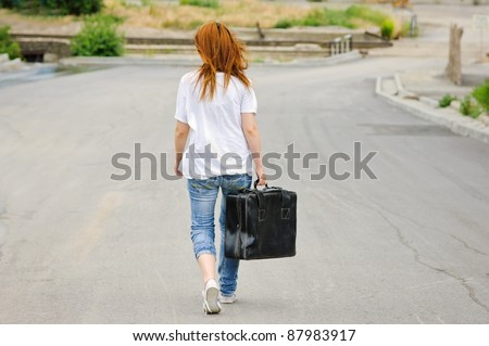 Young girl with old suitcase walking down the street. Rear view - stock photo