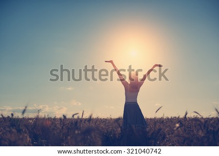 Young girl with outspread hands have fun at sunset in the field (intentional sun glare and vintage color)