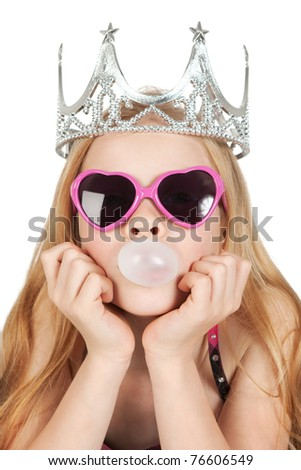 Young girl with princess crown and glasses are making a bubble from the gum over white - stock photo