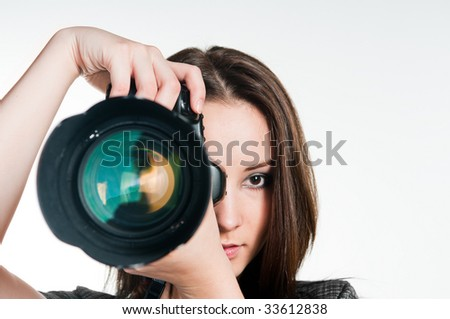Young girl with professional camera, studio shot - stock photo