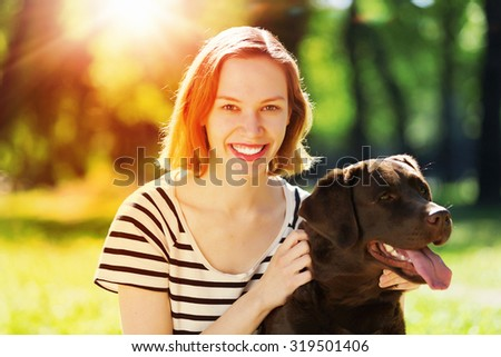 Young girl with retriever on walk in summer park - stock photo