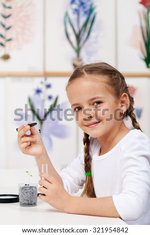 Young girl with seedling for study in biology class - holding a small plant and smiling - stock photo