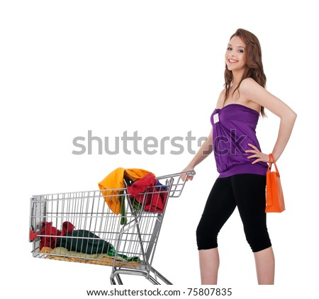 Young girl with shopping cart buying colorful clothes, isolated on white.