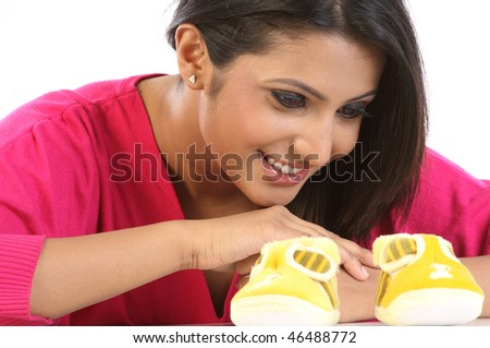 Young girl with small baby shoes - stock photo