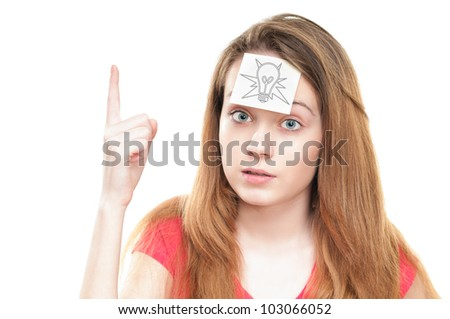 Young girl with small note paper on her forehead. Inspiration or idea concept. Looking into the camera, holding her hand with finger up. Isolated on white background. - stock photo