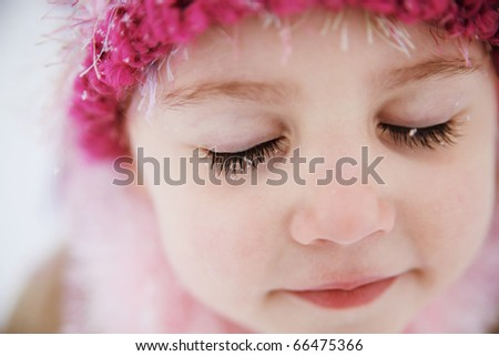 Young girl with snowflakes on long dark eyelashes wearing a hat outdoors in winter. - stock photo