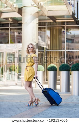 young girl with suitcase in city