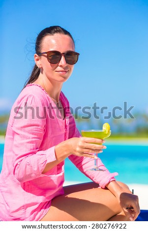 Young girl with tasty cocktail on white tropical beach - stock photo