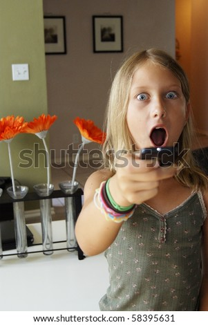 Young girl with Television Remote Control Looking Shocked - stock photo