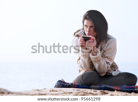 Young girl with the cup of tea in her hands against a sea