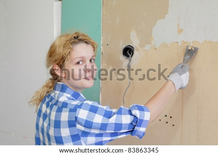 Young girl  with tool in hands taking off wallpaper