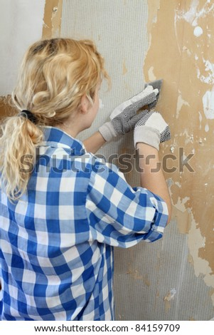 Young girl  with tool in hands taking off wallpaper,  focus on hand