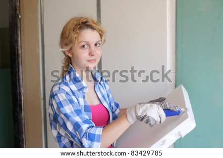 Young girl  with tool in hands working at home improvement