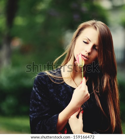 Young girl with tulip. Outside portrait.