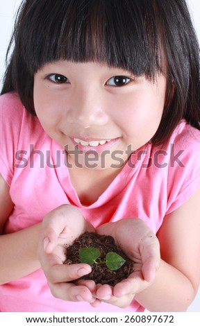 Young girl with two hands holding sapling soil. - stock photo