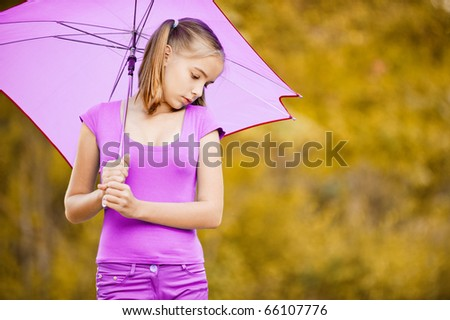 Young girl with violet umbrella looks dow and longs, on autumn background. - stock photo