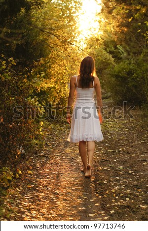 Young girl with white dress walking onto a mysterious path in the forest - stock photo
