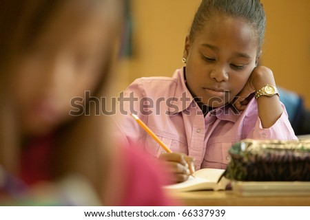 Young girl working in classroom - stock photo