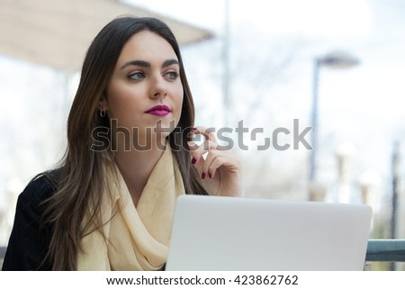 young girl working on her computer / portrait of Beautiful woman using laptop at cafe - stock photo