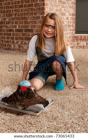 Young girl working on volcano type demonstration for school science project, end result of volcano type demonstration - stock photo