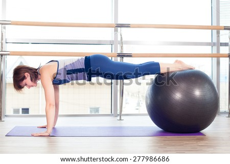 Young girl working out at the gym with a ball.