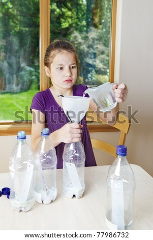 Young girl works on her Science Fair project - pouring in vinegar but worried she'll spill - stock photo