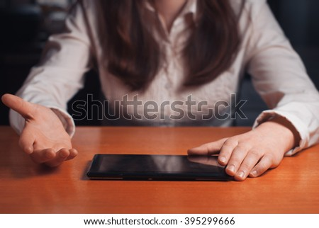 young girl works on the tablet at the table, surfing the Internet