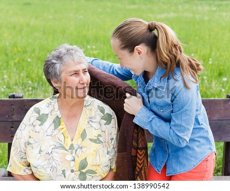 Young girl wrap her mother with a warm sweater - stock photo