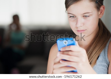 Young girl writing a message with phone - sexual abuse - stock photo