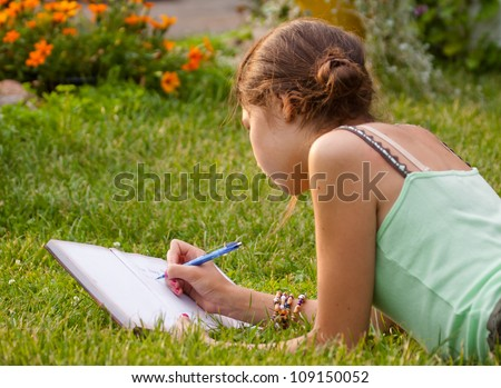 Young girl writing into her notebook - stock photo