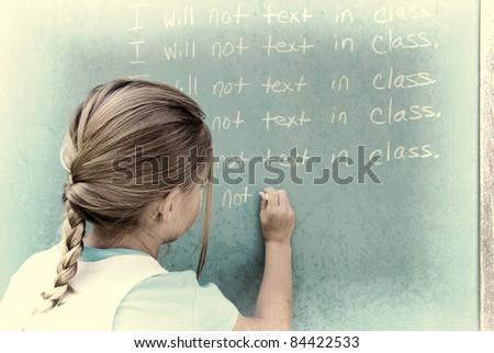 young girl writing lines on chalkboard in textured effect