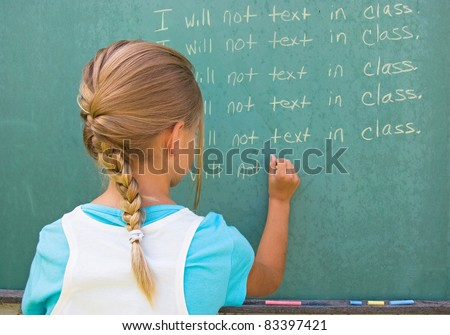 young girl writing lines on green chalkboard.